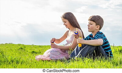 Two kids blowing up the soap bubbles on lawn - Two kids...