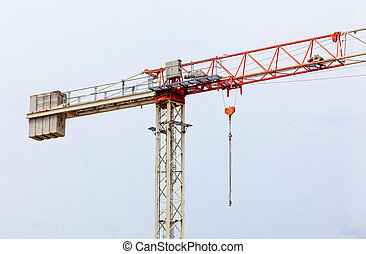 Red and white hoisting crane on blue sky