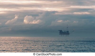 Oil Rig At Sunset - Oil platform rig out at sea in beautiful...