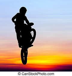 silhouette of motocross rider jump in the sky at sunset