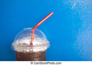 Iced americano on blue wall