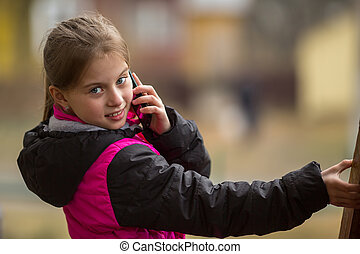 Little girl talking on mobile phone standing on the street.