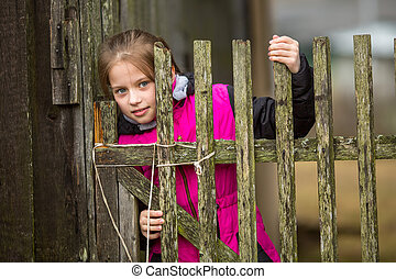Little girl standing behind a fence