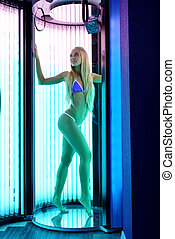 Image of leggy blonde tans in tanning booth - Photo of leggy...