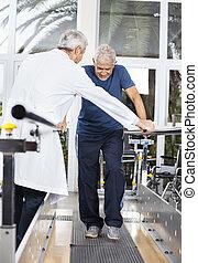 Doctor Examining Senior Man Walking In Fitness Studio