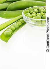 Fresh green pea pods and peas in bowl, on white background...
