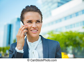 Happy business woman in office district talking smartphone -...