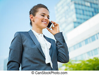 Smiling business woman in office district talking mobile...