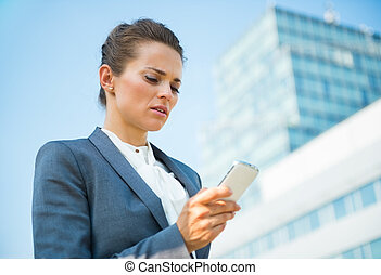Business woman in modern office district reading sms - Into...