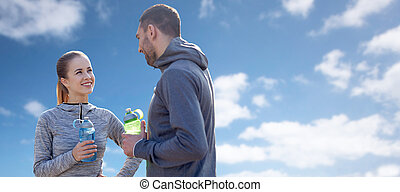 smiling couple with bottles of water over blue sky -...