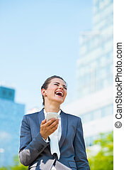 Laughing business woman with smartphone in office district -...