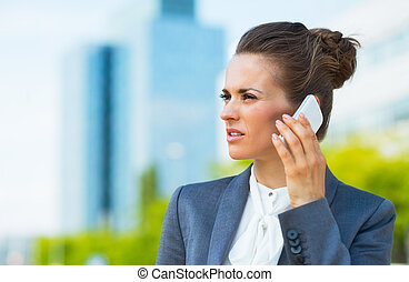 Business woman in modern office district talking smartphone...