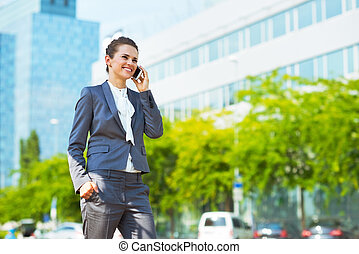 Happy business woman in modern office district talking...