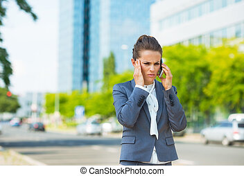 Stressed business woman in office district talking...