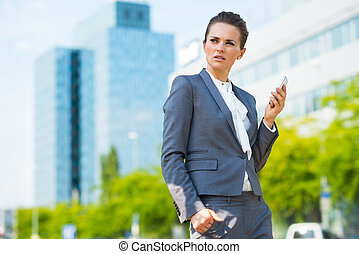 Business woman with cell phone in modern office district -...