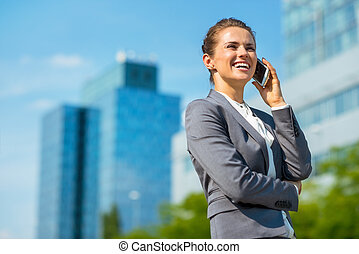 Smiling business woman in office district talking cellphone...