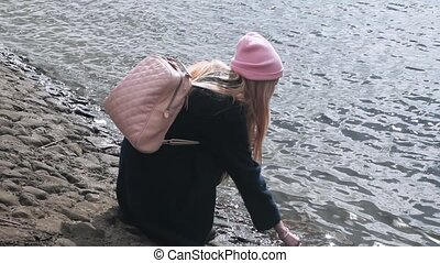 Teen blond girl in pink hat goes up on a stone embankment....