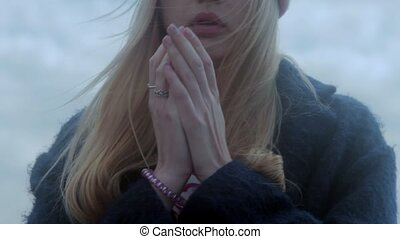Teenage caucasian girl warming hands with breathing -...
