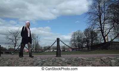 Beautiful blond teen girl walking on the sidewalk around park. She is a young