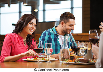 happy couple with friends eating at restaurant - leisure,...