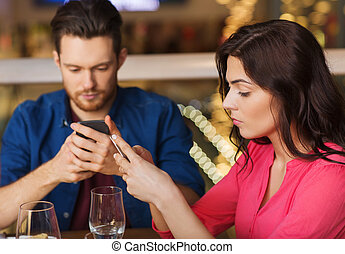 couple with smartphones dining at restaurant - leisure,...