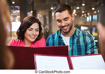 smiling couple with friends and menu at restaurant -...