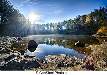 Beautiful lake with rocky shore surrounded with fall colored...
