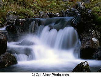 Flowing water of mountain waterfall