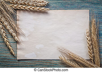 Bunch of wheat rye ears blank vintage sheet paper on wood...