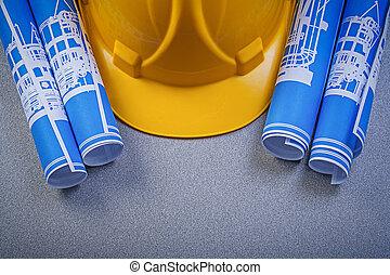 Building helmet blue rolled blueprints on grey background...