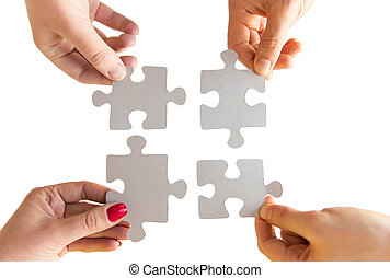 close up of hands connecting puzzle pieces - business,...