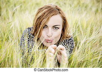 Young positive brunette woman posing in the wheat field,...