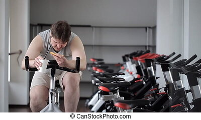 Thick guy practices on an exercise bike, stopping to eat...