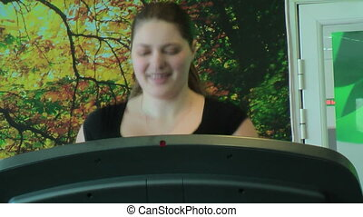 Woman runs on racetrack simulator - Woman does exercise on...