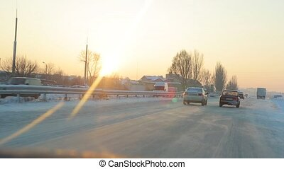 Driving at sunrise on the winter road city.
