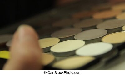 Makeup artist uses a brush and palette eye shadow - Makeup...