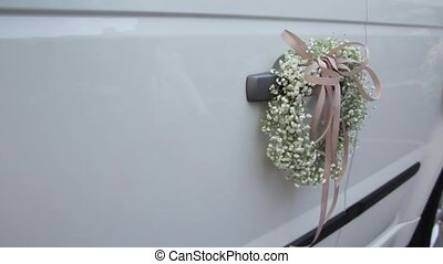 Wedding car decorated with wedding flowers on the door...