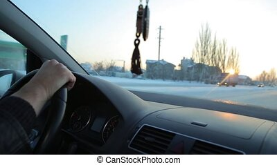 Driving at sunrise. Hand on steering wheel close up. -...