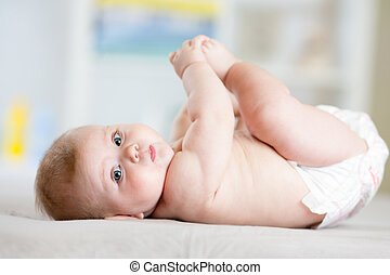 Plump baby lying down on a blanket and holding his feet -...