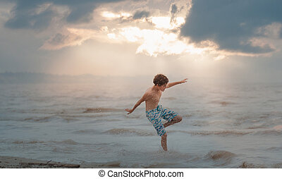 boy jumping in waves