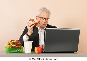 Senior business man eating bread - Senior business man with...