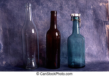 Three old empty bottles on painted background