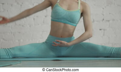Beautiful Young Woman Doing Yoga Workout In a Stretching...