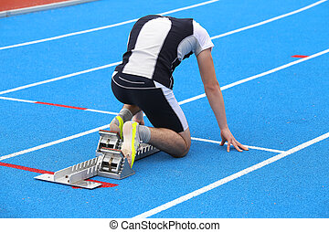 muscular young athlete in the starting blocks of a athletic...