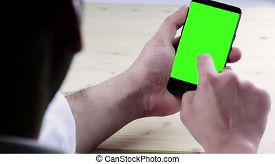 man hand using a smart phone with chroma key on wood table...