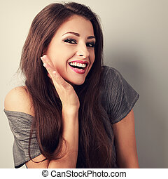 Happy toothy laughing brunette young woman with hand near...