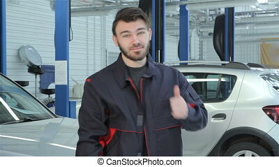 Mechanic shows his thumb at the car service - Bearded...