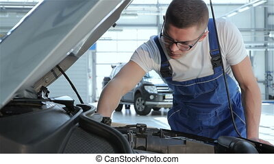 Mechanic checks up serviceabillity of the car - Blond...