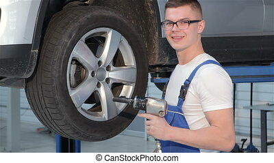 Mechanic holds pneumatic wrench in his hand