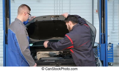 Two mechanics open the car hood at the car service - Two...